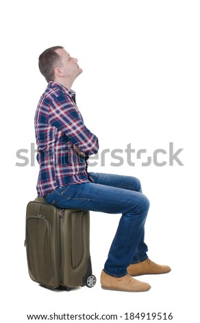 back view man sitting on  suitcase. waiting at station. backside view person.  Rear view people collection. Isolated over white background. guy with travel bag on wheels looking at something at top