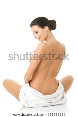 Back view nude woman sitting wrapped in towel.