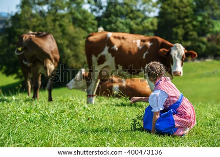 Back view of a adorable little  bavarian girl on a country field with cow in Germany - stock photo