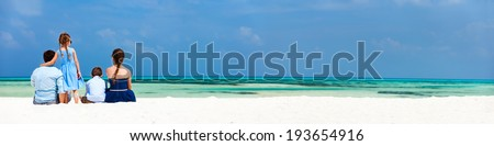 Back view of a beautiful family on a beach during summer vacation. Panorama perfect for banners - stock photo