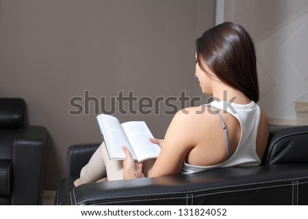 Back view of a beautiful woman at home sitting on a couch reading a book.