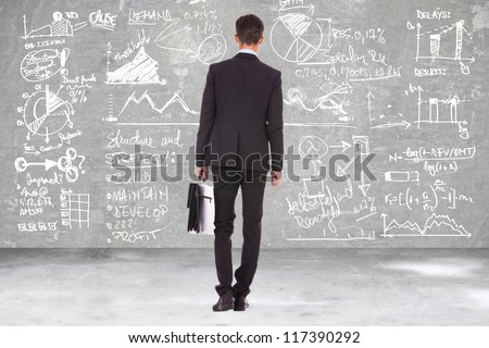 back view of a business man holding a briefcase and looking at some charts , graphs and calculations on a blackboard - stock photo