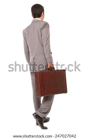 back view of a business man standing and holding a briefcase, isolated on white background - stock photo