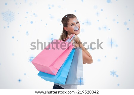 Back view of a cheerful woman holding shopping bags against snow falling - stock photo