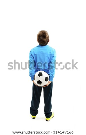 Back view of a child in sportswear holding a soccer ball. Isolated on white background - stock photo