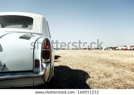 Back view of a classic car parked in a field - stock photo