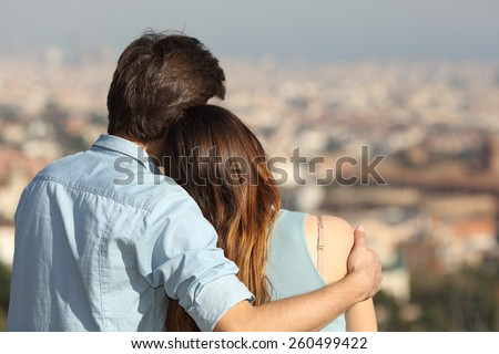 Back view of a couple dating in love hugging and looking the city in a sunny day - stock photo