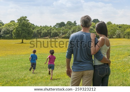 back view of a couple holding each other and contemplating a landscape while their two children running in the grass - stock photo