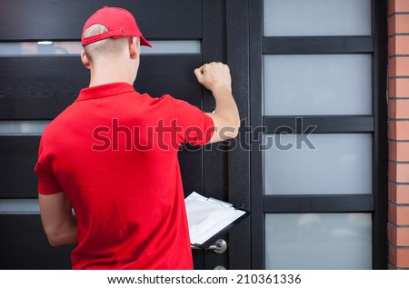 Back view of a delivery man knocking on the client's door - stock photo