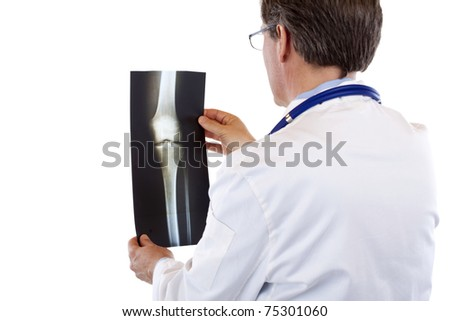 Back view of a doctor studying knee radiogram.Isolated on white background. - stock photo