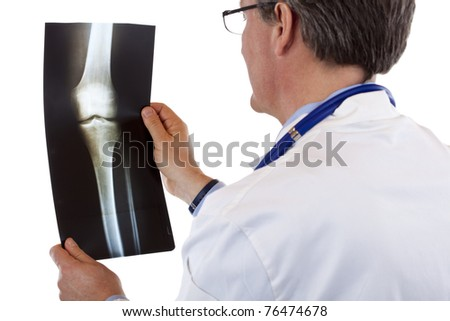 Back view of a doctor studying knee x-ray.Isolated on white background.