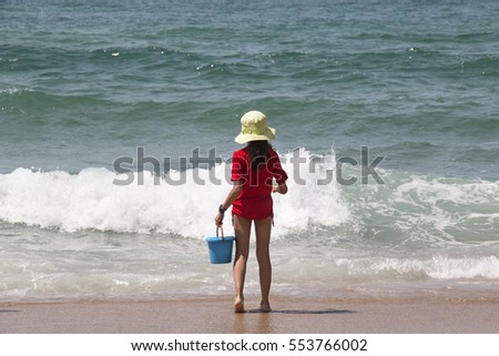 Back view of a girl playing at a beach in Brazil.