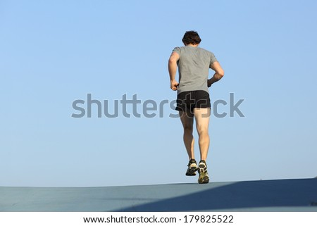 Back view of a jogger man running against blue sky with copy space  - stock photo