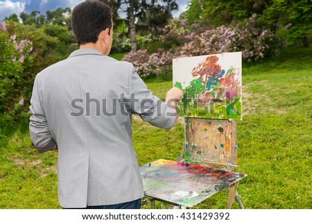 Back view of a male artist painting a standing in front of  a sketchbook during creation a beautiful sketch of picture outdoors - stock photo