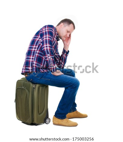 back view of a man sitting on a suitcase. waiting at the station. backside view of person. Isolated over white background. guy with a travel bag on wheels looking at something at the top