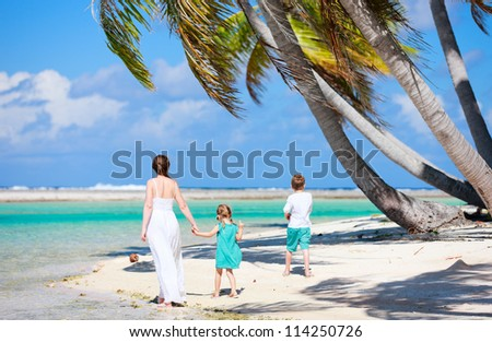Back view of a mother walking with her two kids along a tropical beach - stock photo