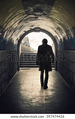 Back view of a mysterious man walking in a padestrian tunnel - stock photo