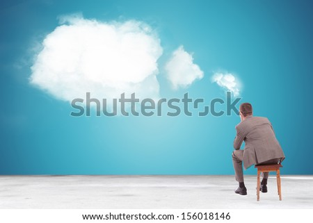 back view of a pensive business man looking at a speech bubble made of clouds
