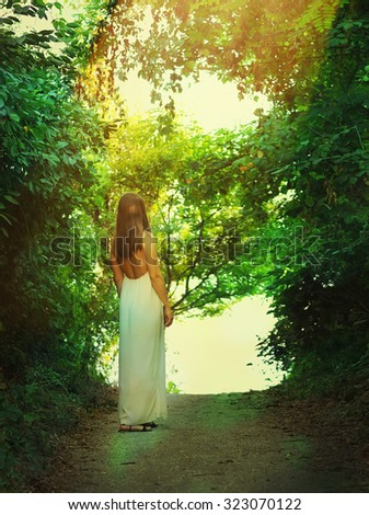 Back view of a slim fashion woman dressed in long white dress illuminated by sunlight standing on a forest way. - stock photo