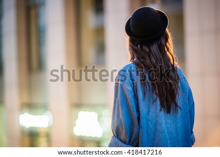Back view of a stylish female tourist in black hat. The girl walks on a night city. Beautiful brunette girl with long hair in black bowler hat and a denim shirt.