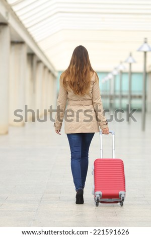 Back view of a tourist woman walking and carrying a suit case in an airport or station - stock photo