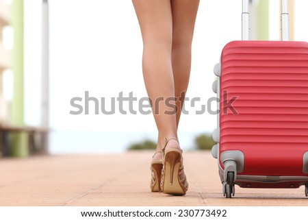 Back view of a traveler woman legs walking with a suitcase in the street towards the beach with copyspace - stock photo