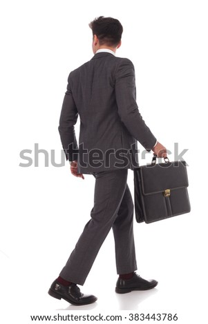 back view of a walking businessman with briefcase looking to his side on white studio background