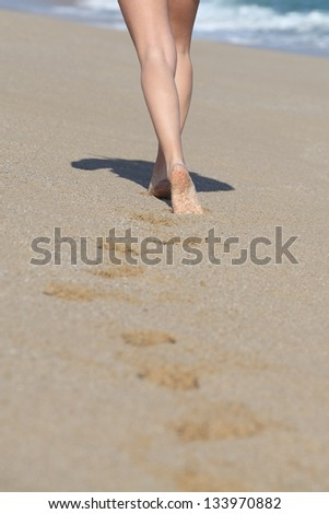 Back view of a woman legs walking on the beach and her traces with the sea in the background