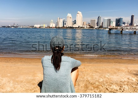 Back view of a woman sitting on beach and looking out into bay of San Diego, California.