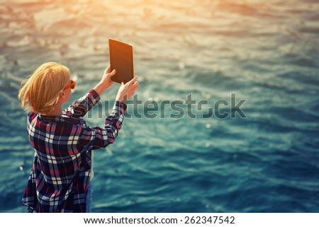 Back view of a woman taking picture with a digital tablet camera standing against sea background on the beach, female tourist standing on coastline photographing nature view, flare sun light, filter - stock photo