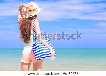 back view of a woman with stripy bag and straw hat at tropical beach - stock photo