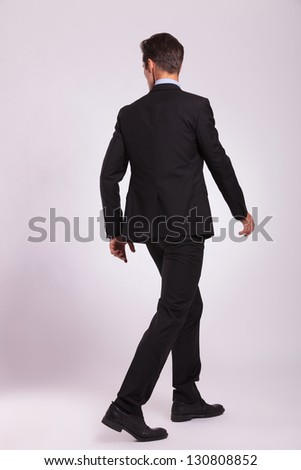 back view of a young business man walking and looking to his side, on gray background - stock photo