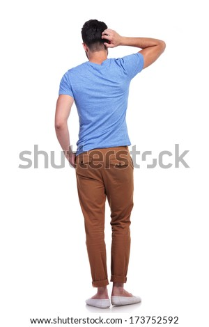 back view of a young confused casual man scratching his head on white background - stock photo