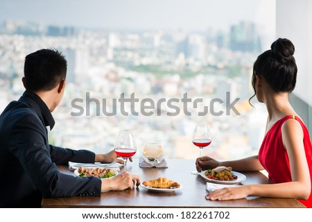 Back view of a young couple while their romantic dating looking through the window on the foreground