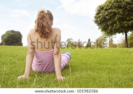Back view of a young girl sitting down on green grass in the park, looking at the horizon. - stock photo