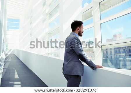 Back view of a young intelligent male lawyer thinking about something while looking in big office window, confident serious prosperous man economist dressed in suit enjoying calm after hard work day - stock photo