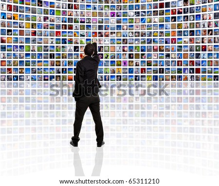 Back view of a young man watching a big TV panel - stock photo