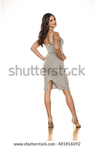 back view of a young pretty woman standing in a short dress and high heels
