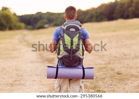 Back view of a young tourist wearing blue t-short and beige shorts with a big traveling backpack walking in the countryside  - stock photo