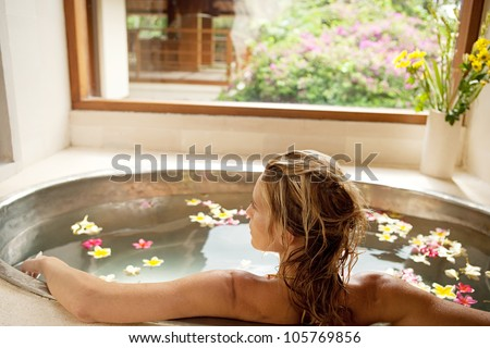 Back view of a young woman bathing in a health spa's flower bath. - stock photo