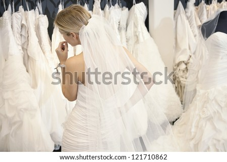 Back view of a young woman in wedding dress looking at bridal gowns on display in boutique - stock photo