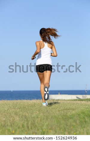 Back view of a young woman running on the grass towards the sea - stock photo