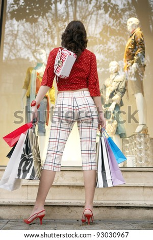 Back view of a young woman standing by a shop window, holding shopping bags. - stock photo