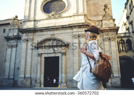 Back view of a young woman traveler with a backpack on her shoulder out sightseeing in a foreign city, stylish female foreigner examines architectural monument during her long-awaited summer vacation - stock photo