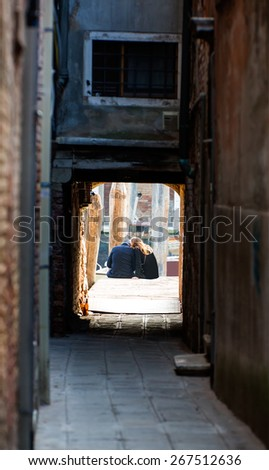 Back view of affectionate couple sitting on the pier and looking at venice canal - stock photo