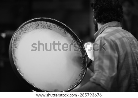 Back view of an asian musician playing daf drum, persian music - stock photo
