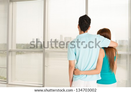Back view of an embracing couple looking out of the window - stock photo