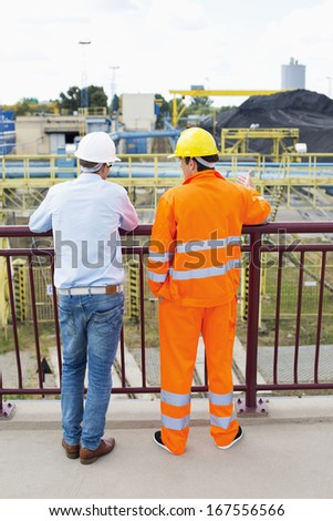 Back view of architects standing against railing at construction site - stock photo