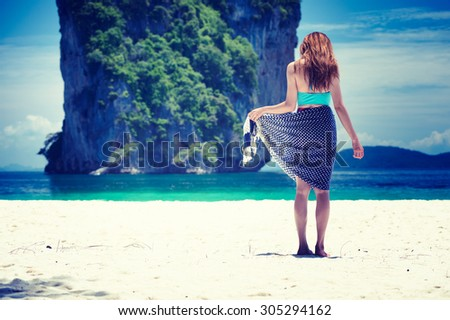 Back view of asia beautiful woman with dress and bikini standing on Phiphi Island in summer, krabi, Thailand - stock photo