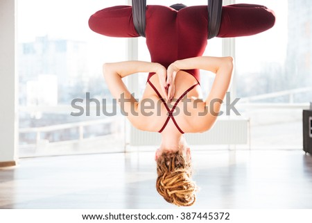 Back view of attractive young woman doing pose of antigravity yoga in studio - stock photo